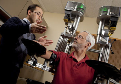 Scientists discussing robotic system KINARM